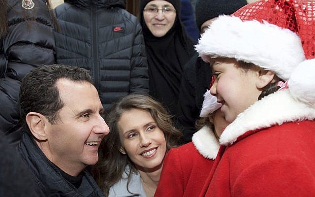A Syrian orphan dressed as Santa Claus meets with Syrian President Bashar Assad, left, and his wife Asma, center, during a visit to Sednaya Convent on December 25, 2016. (AP/Syrian Presidency via Facebook)