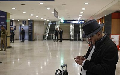A traveler checks his smartphone inside Orly airport, south of Paris March, 18, 2017. AP Photo/Kamil Zihnioglu)
