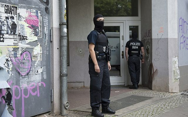 Illustrative: Masked police stand outside a house in Berlin on July 12, 2017, after special police units raided several homes in connection with a 100-kilogram gold coin stolen from the Bode Museum.  (Paul Zinken/dpa via AP)