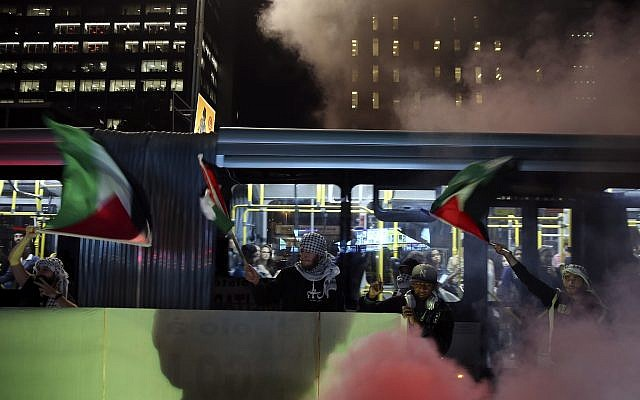 Demonstrators light flares and hold Palestinians flags as they protest against clashes in Gaza and the transfer of the US embassy to Jerusalem, in Sao Paulo, Brazil, Tuesday, May 15, 2018. (AP/Andre Penner)