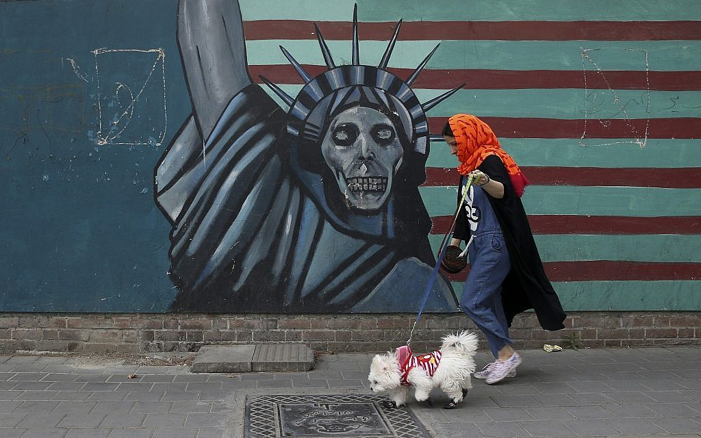 A woman walks her dog past a satirical drawing of Statue of Liberty on the wall of the former US Embassy in Tehran, Iran, May. 8, 2018. (Vahid Salemi/AP)