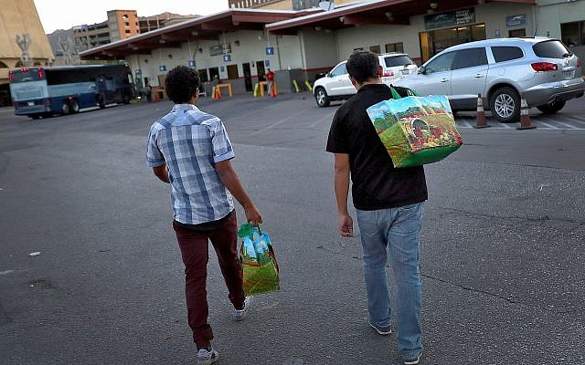 Wilson Romero, left, and Daniel Montes, both from Honduras, arrive at a bus terminal early  June 27, 2018, in El Paso, Texas (AP Photo/Matt York)