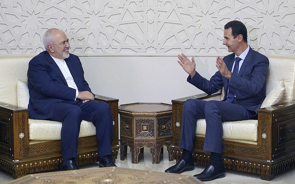 In this photo released by the Syrian official news agency SANA, Syrian President Bashar Assad, right, speaks with Iranian Foreign Minister Mohammad Javad Zarif in Damascus, Syria, Sept 3, 2018. (SANA via AP)