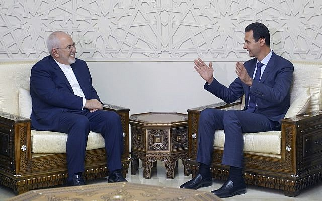 Illustrative: In this photo released by the Syrian official news agency SANA, Syrian President Bashar Assad, right, speaks with Iranian Foreign Minister Mohammad Javad Zarif in Damascus, Syria, Sept 3, 2018. (SANA via AP)