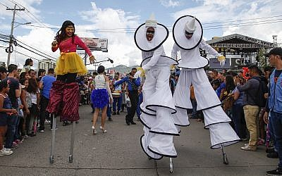 Performers on stilts dance for the crowd during the Founders' Anniversary Festival in Tegucigalpa, Honduras, Saturday, Sept. 22, 2018. (AP/Fernando Antonio)