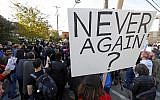 A person holds a sign during a protest gathering on the block of the Jewish Community Center in the Squirrel Hill neighborhood of Pittsburgh, where the funeral for Dr. Jerry Rabinowitz, Tuesday Oct. 30, 2018. (AP/Gene J. Puskar)