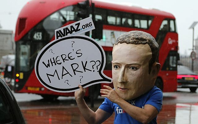"An activist wearing a Facebook CEO Mark Zuckerberg mask stands outside Portcullis House in Westminster as an international committee of parliamentarians met for a hearing on the impact of disinformation on democracy in London, Tuesday, Nov. 27, 2018. Lawmakers from nine countries grilled a Facebook executive who came in place of Zuckerberg on Tuesday as part of an international hearing at Britains parliament on disinformation and ""fake news."" (AP Photo/Frank Augstein)"