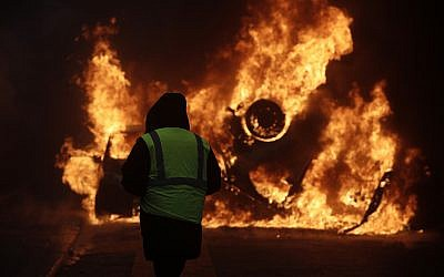 A demonstrator watches a burning car near the Champs-Elysees avenue during a demonstration, Dec.1, 2018 in Paris (AP Photo/Kamil Zihnioglu)
