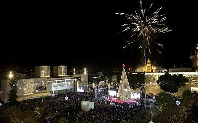 Christians celebrate the lighting of a Christmas tree in Manger Square, outside the Church of the Nativity in the West Bank town of Bethlehem, Dec. 1, 2018. (AP Photo/Majdi Mohammed)