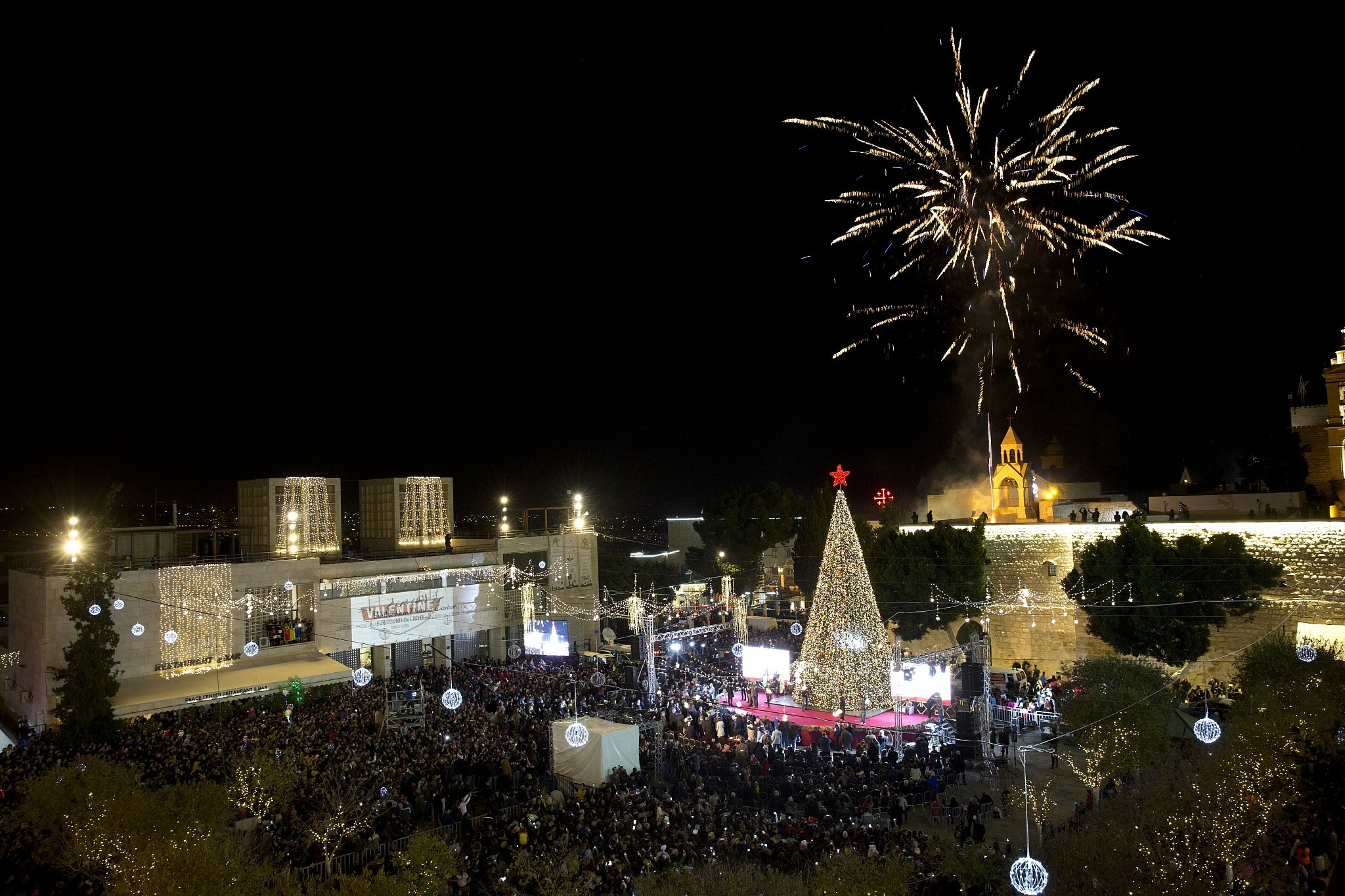 Christians celebrate the lighting of a Christmas tree in Manger Square, outside the Church of