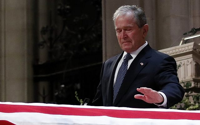 Former president George W. Bush touches the casket of his father, former president George H.W. Bush, at the State Funeral at the National Cathedral, Wednesday, Dec. 5, 2018, in Washington.(AP Photo/Alex Brandon, Pool)