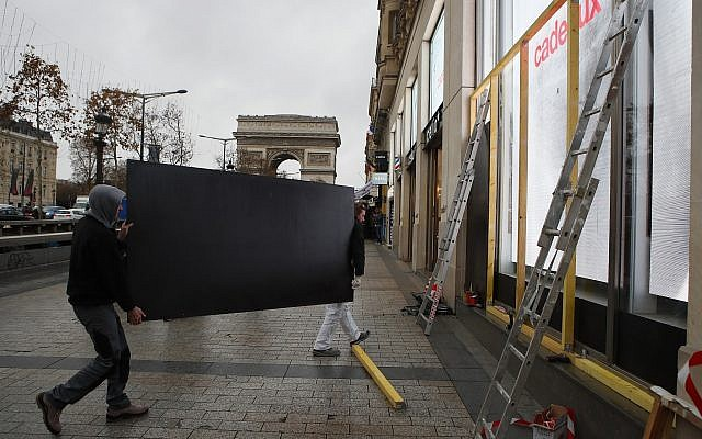 Workers carry a wooden piece to protect shop windows on the Champs-Elysees avenue, Friday, Dec. 7, 2018 in Paris (AP Photo/Francois Mori)