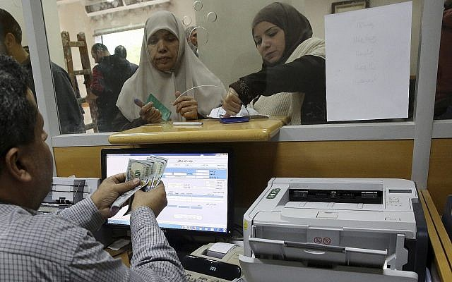 A Hamas-appointed government employee in Gaza signs a document to receive 50 percent of her long-overdue salary from funds donated by Qatar, while others wait in the queue, at the main Gaza Post Office, in Gaza City, December 7, 2018. (AP Photo/Adel Hana)
