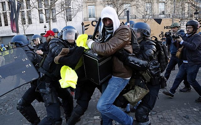 Police apprehend a 'yellow vest' demonstrator on the Champs Elysees in Paris, France, on Saturday, December 8, 2018. (AP/Thibault Camus)