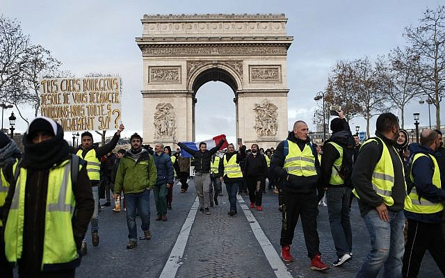 Demonstrators wearing yellow vests march down the Champs Elysees avenue Saturday, Dec. 8, 2018 in Paris (AP Photo/Thibault Camus)
