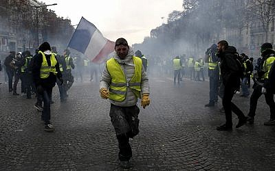 A demonstrator wearing a yellow vest grimaces through tear gas, Dec. 8, 2018 in Paris (AP Photo/Rafael Yaghobzadeh)