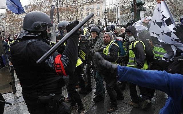 Police officers clash with demonstrators wearing yellow vests in Paris on December 8, 2018 (AP Photo/Thibault Camus)