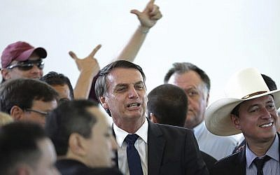 Brazil's president-elect Jair Bolsonaro, center, poses for photos during a lunch with popular singers who supported his campaign, at the Army Club, in Brasilia, Brazil, Tuesday, Dec. 11, 2018. (AP/Eraldo Peres)