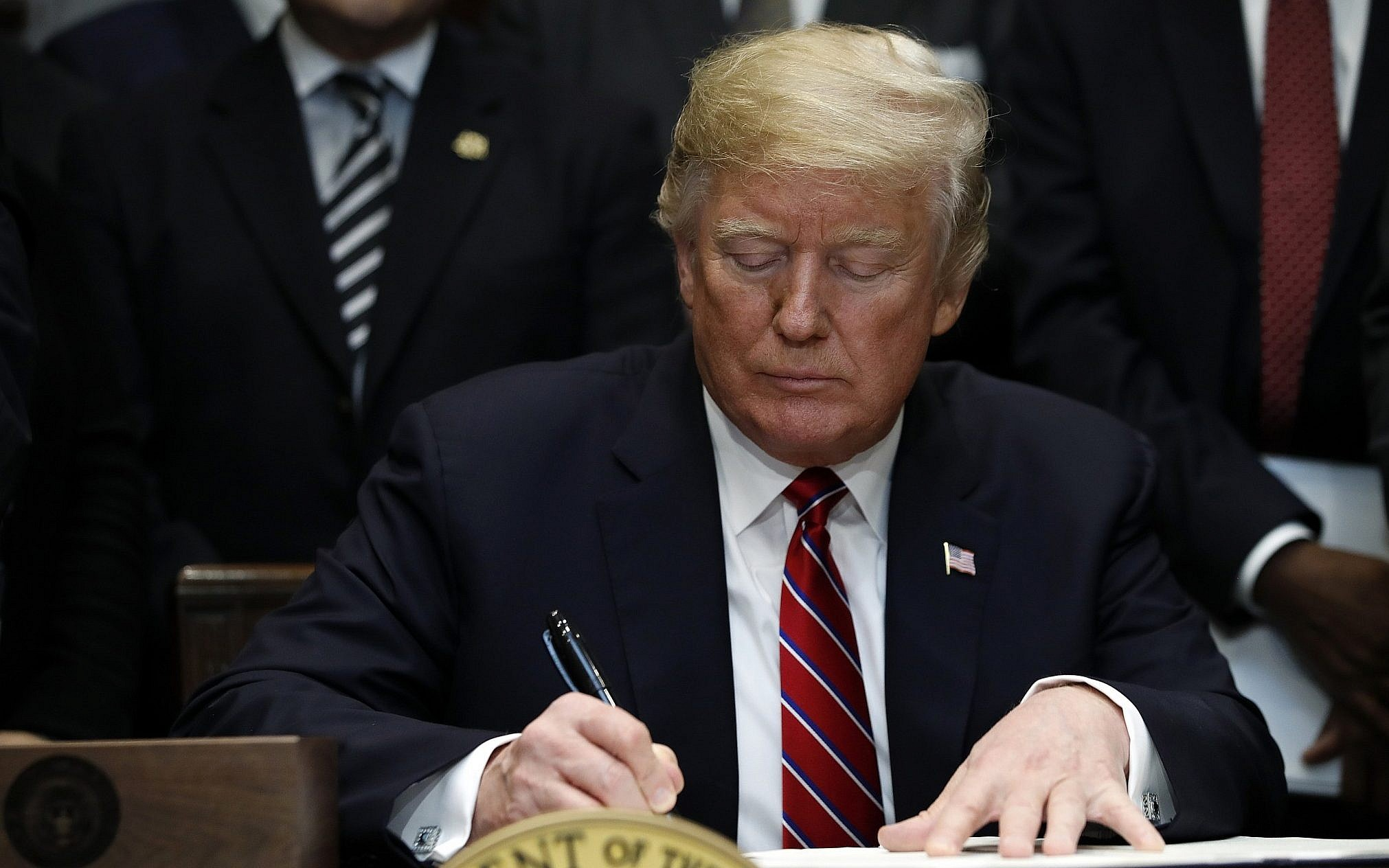 US President Donald Trump signs an executive order in the Roosevelt Room of the White House Washington
