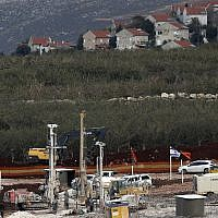 In this Thursday, Dec. 13, 2018 photo, Israeli military equipment works on the Lebanese-Israeli border in front of the Israeli town of Metula, background, near the southern village of Kafr Kila, Lebanon (AP Photo/Hussein Malla)