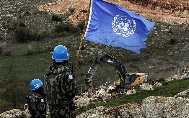 In this Thursday, Dec. 13, 2018 photo, UN peacekeepers hold their flag, as they observe Israeli excavators working near the southern border village of Mays al-Jabal, Lebanon. (AP/Hussein Malla)