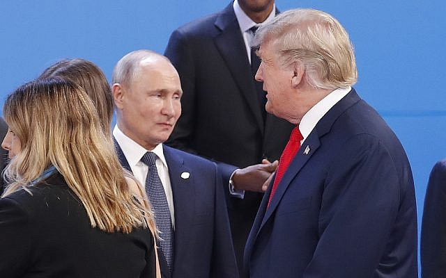 In this photo from November 30, 2018, US President Donald Trump, right, walks past Russia's President Vladimir Putin, left, as they gather for the group photo at the start of the G20 summit in Buenos Aires, Argentina. (AP Photo/Pablo Martinez Monsivais, File