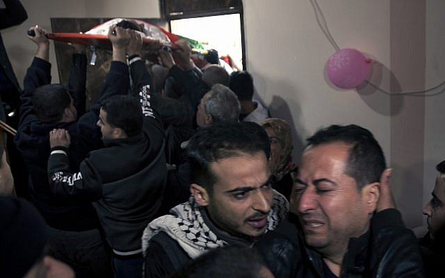 Relatives of 16 year-old Palestinian Mohammed Jahjouh, who was said to have been shot and killed by Israeli troops during a protest at the Gaza Strip's border with Israel, mourn as others carry his body into the family home during his funeral in Gaza City, December 22, 2018. (AP Photo/Khalil Hamra)