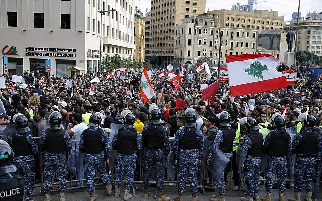 Anti-government protesters hold Lebanese flags and chant slogans as riot police stand guard in front of the government building, in central Beirut, Lebanon, Dec. 23, 2018 (AP Photo/Bilal Hussein)