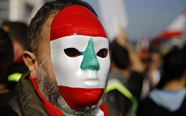 An anti-government protester wears mask mimicking the Lebanese flag during a protest in downtown Beirut, Lebanon, Dec. 23, 2018 (AP Photo/Bilal Hussein)