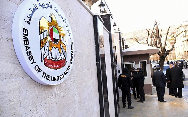 In this photo released by the Syrian official news agency SANA, officials and journalists gather outside the embassy of the United Arab Emirates, in Damascus, Syria, Thursday, Dec. 27, 2018. (SANA via AP)