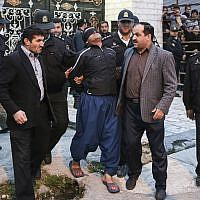 This Tuesday, April 15, 2014, file photo provided by ISNA, a semi-official news agency, shows blindfolded Iranian convicted man Bilal being escorted by officials and security to be prepared for his execution in public in the northern city of Nour, Iran. He was later pardoned moments before being hanged. (AP/ISNA, Arash Khamoushi)
