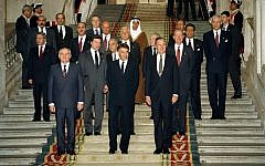 From left front, Soviet President Mikhail Gorbachev, Spanish Premier Felipe Gonzales and US President George H.W. Bush pose in front of delegates at the end of the first session of the Middle East peace conference held in the Palacio Real in Madrid, Spain, on October 30, 1991. (AP Photo/Jerome Delay)