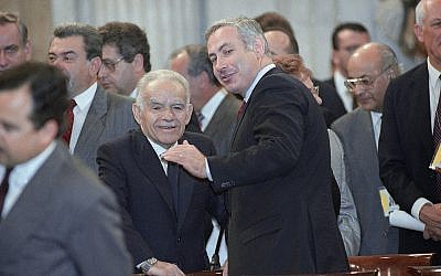 Israeli Prime Minister Yitzhak Shamir, left, confers with Benjamin Netanyahu, a member of the Israel delegation, prior to the start of the opening session of the Mideast peace conference on Oct. 30, 1991 in Madrid. President George H.W. Bush and Soviet President Mikhail Gorbachev opened the conference between Israel and front line Arab States. (AP Photo/Denis Paquin)