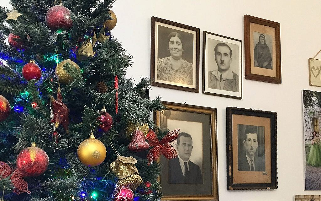 The Christmas tree in Beit Rima, next to photos of the Khoury family. (Federico Maccioni/ Times of Israel)