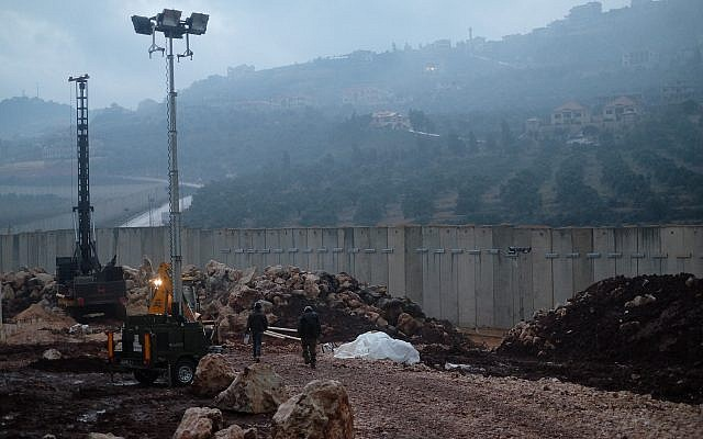 Israeli troops operate next to the entrance point to a tunnel dug into an apple field south of the Israeli town of Metulla from Lebanon on December 19, 2018. (Judah Ari Gross/Times of Israel)