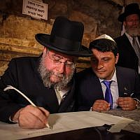 Rabbi Pinchas Goldschmidt, seen writing a new Torah scroll at an event attended by Israeli and European rabbis, marking the Hebrew date of 69 years since the liberation of Jews in Europe, in the Western Wall tunnels, in Jerusalems Old City, May 21, 2014. (Flash90)