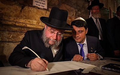 Rabbi Pinchas Goldschmidt, seen writing a new Torah scroll at an event attended by Israeli and European rabbis, marking the Hebrew date of 69 years since the liberation of Jews in Europe, in the Western Wall tunnels, in Jerusalem's Old City, May 21, 2014. (Flash90)