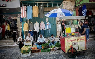 Palestinians shop at a vegetable market in the West Bank city of Bethlehem, August 30, 2018 (Miriam Alster/FLASH90)