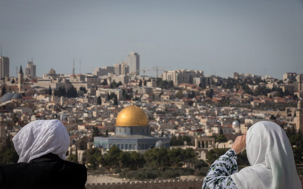 Tourists look at the view of the Dome of the Rock and the Temple Mount from the lookout of the Mount of Olives overlooking the Old city of Jerusalem, on November 28, 2018. (Yonatan Sindel/Flash90)