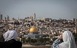 Tourists look at a view of the Dome of the Rock and the Temple Mount from the lookout of the Mount of Olives overlooking the Old city of Jerusalem, on November 28, 2018. (Yonatan Sindel/Flash90)