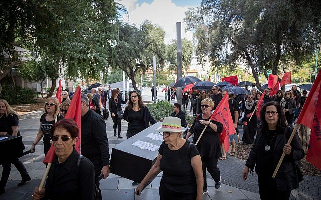 Israeli women hold fake coffins symbolizing the murders of women killed as part of a nationwide strike protesting the violence against women, Tel Aviv, December 4, 2018 (Miriam Alster/Flash90)