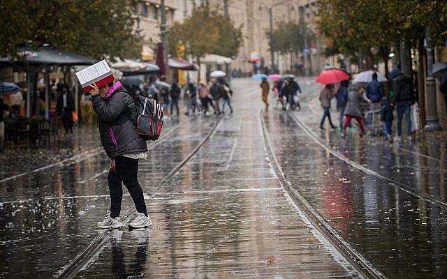 People walk on rain-soaked Jaffa Street in Jerusalem on December 6, 2018. (Yonatan Sindel/Flash90)