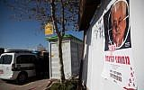 A poster showing Palestinian President Mahmoud Abbas with a text reading 'Assassinate murder funders' hanging on a bus station at the entrance to the Israeli settlement of Geva Binyamin, in the West Bank on December 11, 2018. (Yonatan Sindel/Flash90)