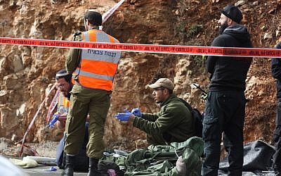 Israeli soldiers, medical officials and police inspect the scene of a terrorist shooting attack near Givat Assaf, in the central West Bank, on December 13, 2018. (Hadas Parush/Flash90)