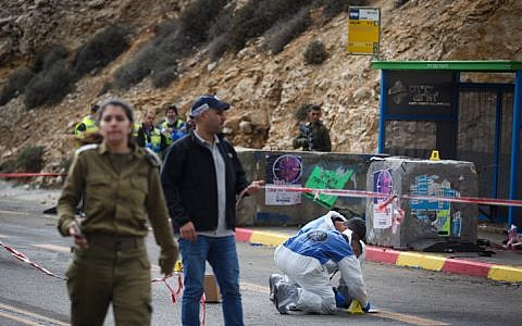 Israeli soldiers, medical officials and police inspect the scene of a shooting attack near Givat Assaf, in the central West Bank, on December 13, 2018. (Hadas Parush/Flash90)