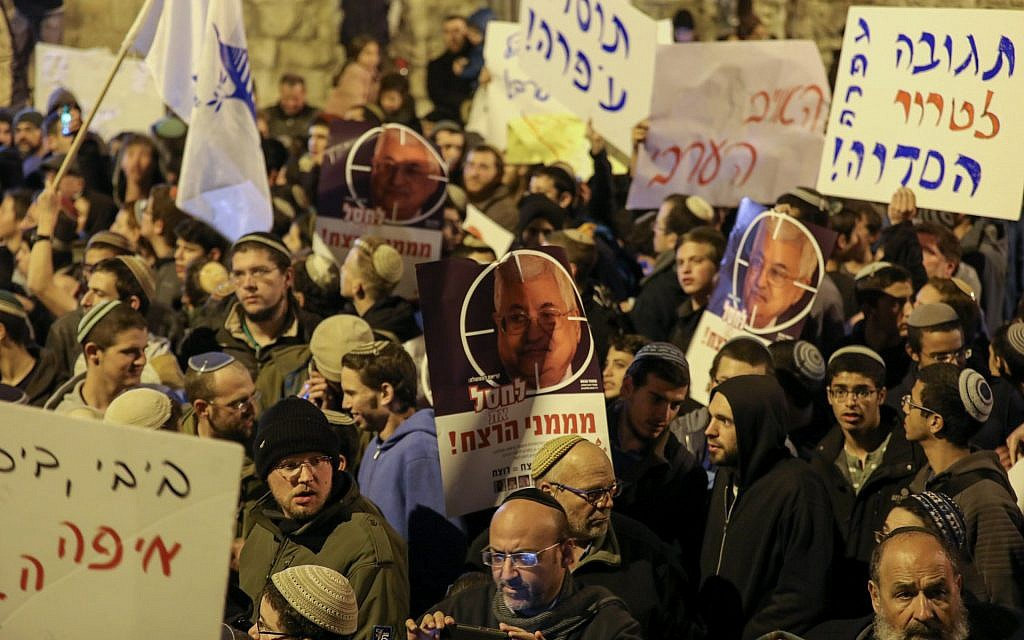 Right-wing Israelis at a protest outside the Prime Minister's Residence in Jerusalem on December 13, 2018, hold signs depicting Palestinian Authority President Mahmoud Abbas in the crosshairs of a rifle scope. (Yonatan Sindel/Flash90)