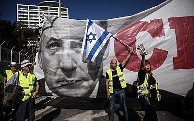 """A poster of Prime Minister Benjamin Netanyahu is seen, as """"yellow vest"""" protests reach Israel with hundreds marching against the rising cost of living in central Tel Aviv on December 14, 2018. (Miriam Alster/Flash90)"""