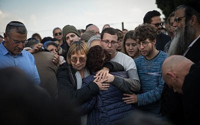 Friends and family mourn by the grave of author Amos Oz during a his funeral in Kibbutz Hulda, on December 31, 2018. (Hadas Parush/ Flash90)