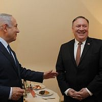 Prime Minister Benjamin Netanyahu (left) and US Secretary of State Mike Pompeo pictured in front of a menorah on the second night of the Hanukkah festival, during their meeting on the sidelines of a NATO conference in Brussels, Belgium, on December 3, 2018. (Gaby Farkash/GPO)