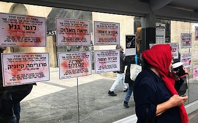 Fliers bearing the names of women murdered in Israel plastered to a bus station in Jerusalem, December 2, 2018. (Luke Tress/ Times of Israel)